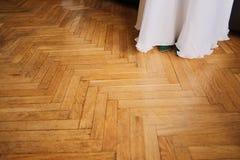 一婚纱的吊边在木地板背景的与闪闪发光的 背景迷离弄脏了抓住飞碟跳的行动 概念:婚礼 库存照片