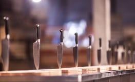 一定数量的刀子在切口厨房板黏附了 暗室 免版税库存照片