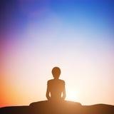 一定的角度瑜伽姿势的妇女思考在日落的 禅宗 免版税库存照片