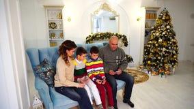 一家之主、父亲和丈夫分布在妻子和男孩之间的家庭预算,坐在欢乐的蓝色沙发 股票录像