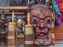 一家佛教古董店的陈列室:与装饰品,打的油的木葡萄酒辅助部件的巨大的木礼节面具 免版税图库摄影