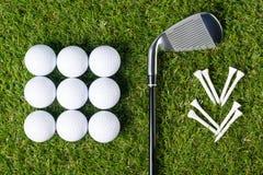一家俱乐部和发球区域,在草背景的高尔夫球材料的想法与球的 免版税图库摄影