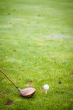 一家司机俱乐部和高尔夫球在领域 库存照片