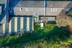 一家工厂的屋顶的垂直的鸟瞰图在一个密集地长得太大的休耕区域旁边的 免版税库存图片