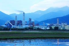 一家工厂的看法在农田中间的有散发烟的烟囱的在清早(深刻的蓝色版本) 免版税库存图片