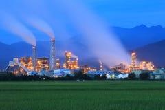 一家工厂的看法在绿色农田中间的在清早微明下 免版税库存图片