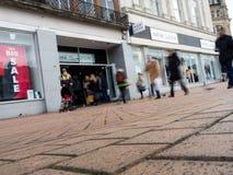 一家新的神色商店的一张正面图有在行动弄脏的步行者的 库存图片