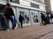 一家新的神色商店的前面有人的在行动捉住了弄脏 库存图片
