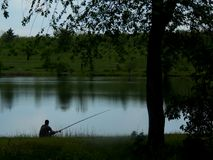 一家绿色银行的一位渔夫有一根钓鱼竿的在一棵大树下坐并且抓鱼 图库摄影
