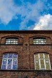 一家老,被破坏的纺织品工厂的门面的片段有被绘的窗口的 库存照片