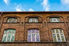 一家老,被破坏的纺织品工厂的门面的片段有被绘的窗口的 免版税库存照片