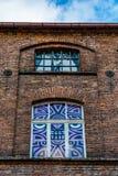 一家老,被破坏的纺织品工厂的门面的片段有被绘的窗口的 免版税库存图片