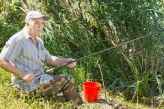 从一家芦苇银行的资深钓鱼者渔 免版税库存照片