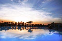 一家豪华度假旅馆的一个大游泳池惊人的日出的 图库摄影