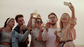 一家非常在屋顶的友好的公司立场,获得乐趣,饮用的鸡尾酒和采取selfies 夏天都市鸡尾酒 股票录像