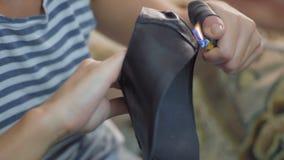 一家鞋厂的女工的特写镜头手在烧焦螺纹的打火机帮助下的黏附在皮革外面 影视素材