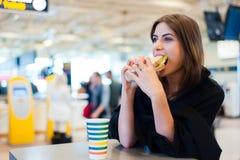 一家餐馆的少妇在国际机场 库存照片