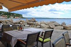 一家餐馆的表和椅子在海的里雅斯特,意大利附近的 免版税库存照片
