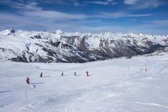 一宽滑雪道,与一个小组滑雪道的滑雪者,在一个清楚的晴天在Meribel,在法国阿尔卑斯 库存照片