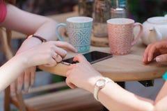 一对一的会议 坐在咖啡馆的桌上的两个少妇 女孩显示她的在智能手机屏幕上的朋友图象  免版税库存图片