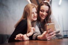 一对一的会议 坐在咖啡馆的桌上的两个年轻女商人 女孩显示她的在智能手机屏幕上的朋友图象  免版税库存图片