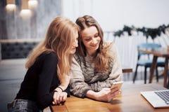 一对一的会议 坐在咖啡馆的桌上的两个年轻女商人 女孩显示她的在智能手机屏幕上的朋友图象  库存照片
