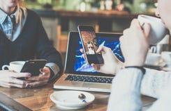 一对一的集会 坐在咖啡馆的桌上的两个年轻女商人 妇女看在智能手机屏幕上的图片 免版税图库摄影