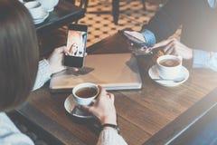 一对一的集会 坐在桌上和使用智能手机的两个少妇 免版税库存图片