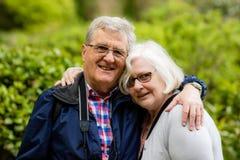 一对亲切的年长夫妇,拥抱和微笑对照相机 库存图片
