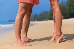 一对亲吻的夫妇的腿在海的靠岸 免版税库存照片