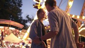 一对华美的年轻夫妇的低角度视图在游乐园在晚上 Hadsome人使他的有棉花的女朋友惊奇 股票录像