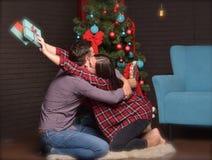 一对可爱的夫妇互相给圣诞节的礼物 宜人的情感 库存照片