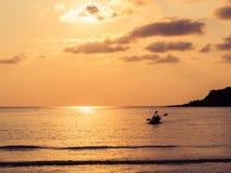一对可爱的夫妇的剪影在一条独木舟小船的在日落期间 库存图片