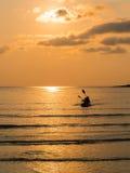 一对可爱的夫妇的剪影在一条独木舟小船的在日落期间 库存照片