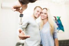 一对可爱的年轻夫妇有钥匙他们新的公寓从不动产房地产经纪商 库存照片