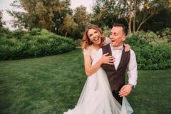 一对可爱的年轻夫妇,佩带一长的轻的白色婚纱和一个新郎的新娘在一个华美的绿色庭院里 贴现女孩桃红色购物口气 库存图片