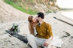 一对在海滩的年轻夫妇亲吻 拥抱在日志的新娘和新郎 特写镜头纵向 免版税库存图片