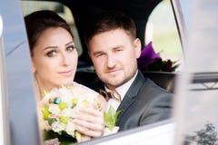 一对在花束旁边的年轻爱恋的夫妇新婚佳偶的画象在婚礼汽车的窗口里 库存照片
