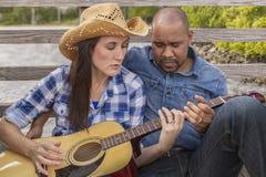 一对多种族夫妇坐学会吉他的甲板 库存照片