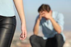 一对夫妇和一个哀伤的人的终止在背景中 免版税库存图片