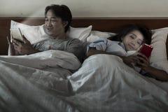 一对夫妇在是对他们的手机感兴趣的床上 不是我 免版税库存照片