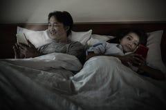 一对夫妇在是对他们的手机感兴趣的床上 不是我 图库摄影
