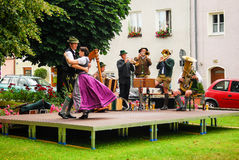 一对夫妇在巴伐利亚跳舞对从一个军乐队的音乐 免版税库存照片