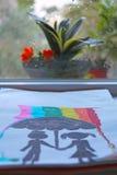 一对夫妇的儿童` s图画在伞下 图库摄影