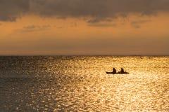 一对夫妇的剪影在一条独木舟小船的在日落期间 库存图片