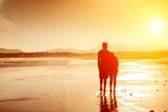 一对夫妇的剪影在海滩的 免版税库存照片