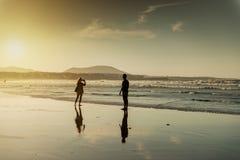 一对夫妇的剪影在海滩的 图库摄影