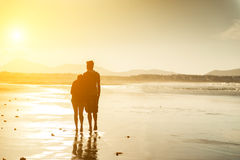 一对夫妇的剪影在海滩的 库存照片