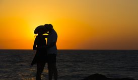 一对夫妇的剪影在爱的在日落的海滩 男孩庭院女孩亲吻的爱情小说 男人和一名妇女海滩的 免版税库存照片
