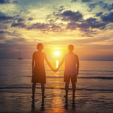 一对夫妇的剪影在他们的站立在海洋的蜜月的靠岸在惊人的日落 库存照片